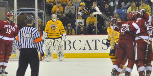 Quinnipiac goalie Eric Hartzell looks on as Harvard players celebrate after Danny Biega scores the game-tying goal in the second period.