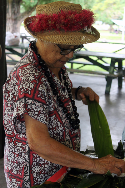 "A Hawaiian woman, part of the ""kupuna,"" or elders, cleans tea leaves to be braided into necklaces."