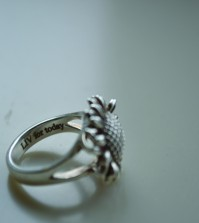 "Brianne wears this sunflower ring that has ""LIV for today"" engraved on it."