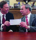 Quinnipiac University President John Lahey presents North Haven First Selectman Michael Freda with a $400,000 check Tuesday, Feb. 1, 2016, at North Haven Town Hall. The annual voluntary contribution to the town is a show of support and partnership between the university and the town.