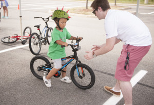 Four-and-a-half-year-old Santino Iamunno, of North Branford, gets one-on-one bike riding instruction from Ian Zane, of Zane's Cycles in Branford, on the second day of Camp No Limits Friday,  July 8, 2016, on Quinnipiac University's York Hill Campus. (Photograph by Autumn Driscoll / for Quinnipiac University)